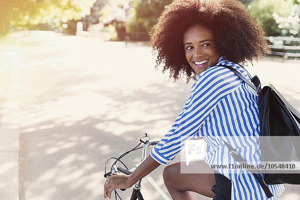 Lächelnde Frau mit Afrofahrrad im Stadtpark