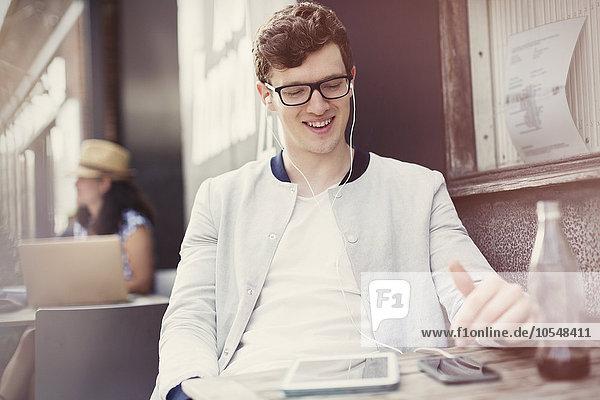 Lächelnder junger Mann hört Musik mit Kopfhörern und mp3-Player auf dem Bürgersteig Cafe