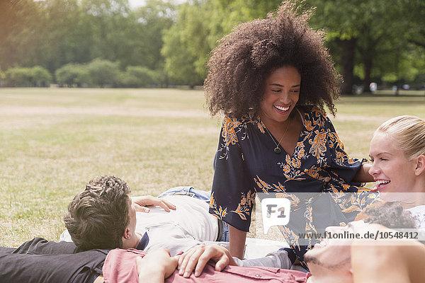 Freunde  die sich im Park auf einer Decke ausruhen.