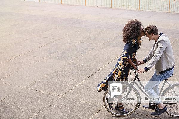 Zärtliche Frau, die den Mann auf dem Fahrrad küsst.