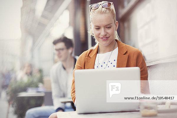 Frau mit Laptop auf dem Bürgersteig Cafe