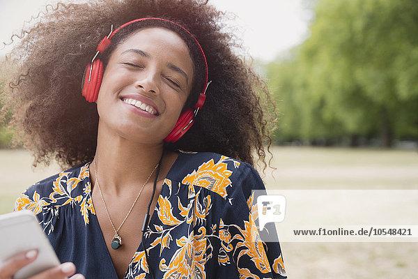 Begeisterte Frau beim Musikhören mit Kopfhörer und mp3-Player im Park
