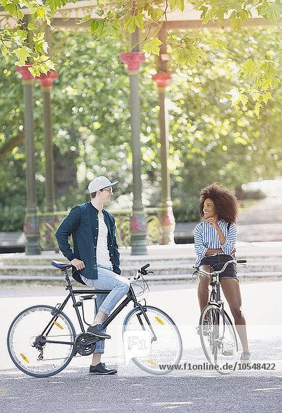 Freunde auf Fahrrädern reden im Stadtpark