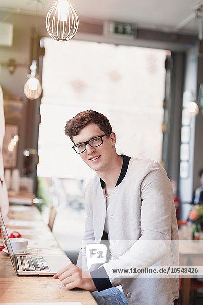 Portrait lächelnder Mann mit Brille mit Laptop im Cafe
