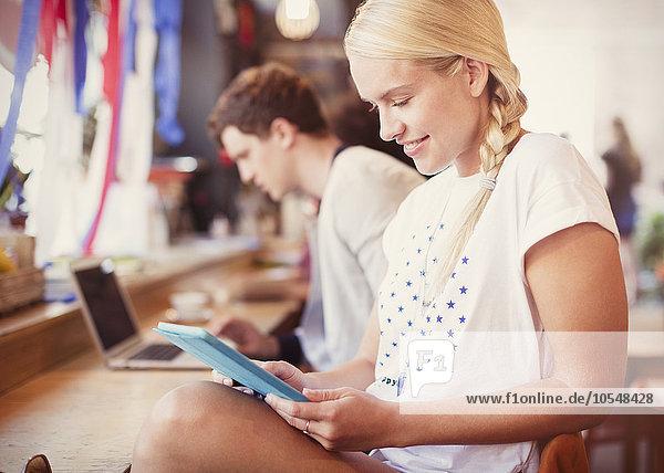 Blonde Frau mit digitalem Tablett im Café