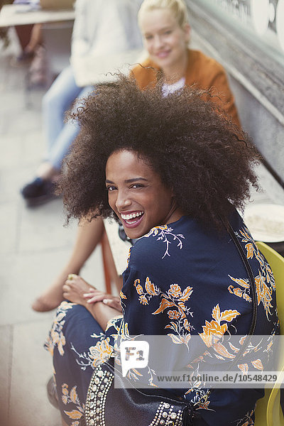 Portrait begeisterte Frau mit Afro im Straßencafé