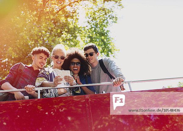 Freunde nehmen Selfie im Doppeldeckerbus mit.