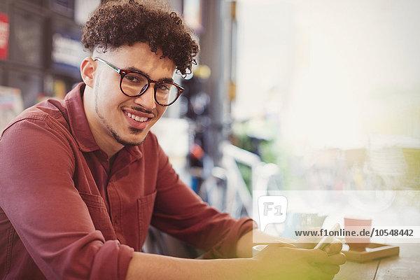 Porträt lächelnder Mann mit lockigen schwarzen Haaren im Cafe