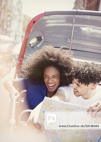Enthusiastisches Paar mit Karte im Doppeldeckerbus