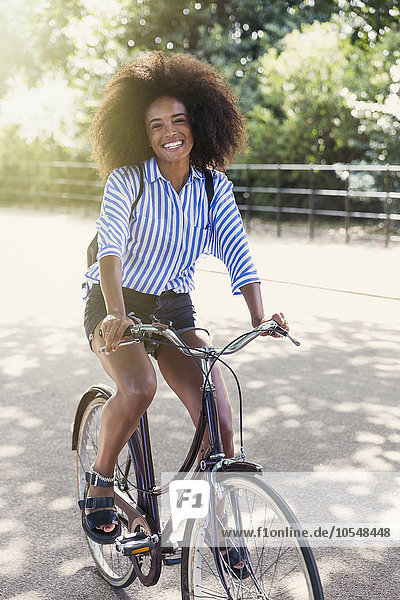 Portrait lächelnde Frau mit Afrofahrrad im Park
