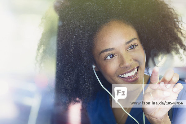 Lächelnde Frau mit Afro- und Kopfhörerzeichnung in Herzform am Busfenster