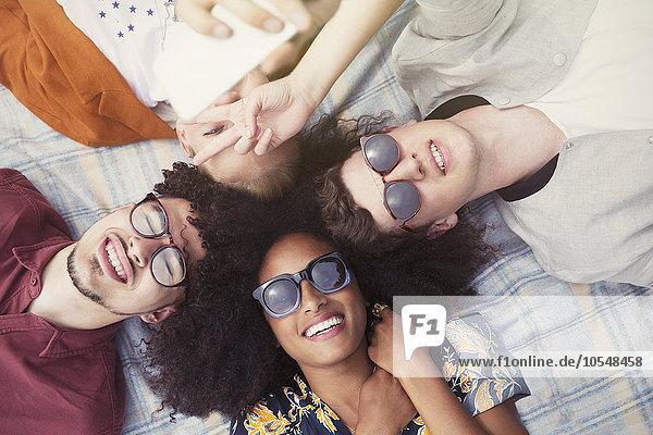 Overhead-Porträt lächelnde Freunde im Kreis auf Decke liegend