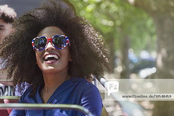 Enthusiastische Frau mit Afro-Brille in Herzform