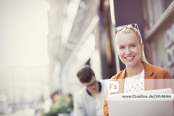 Portrait lächelnde blonde Frau mit Laptop auf dem Bürgersteig Cafe