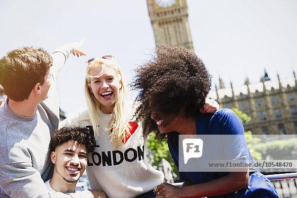 Begeisterte Freunde  die lachen und auf den Big Ben-Uhrturm zeigen  London  Vereinigtes Königreich
