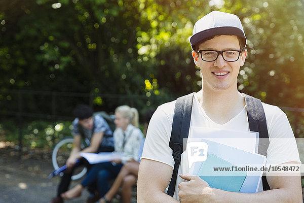 Portrait lächelnder Student mit Büchern im Park