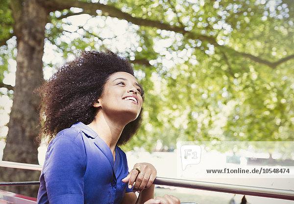 Sorglose Frau mit Afro-Doppeldeckerbus und Blick nach oben