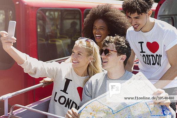 Freunde mit Kartenaufnahme im Doppeldeckerbus