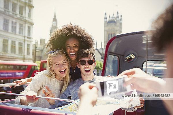 Begeisterte Freunde beim Fotografieren im Doppeldeckerbus