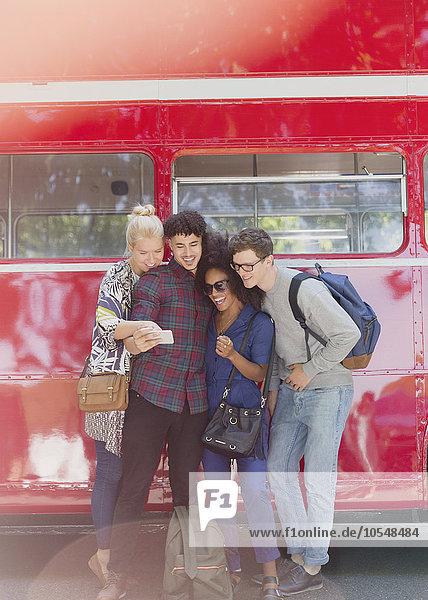 Freunde mit Selfie neben dem Doppeldecker-Bus