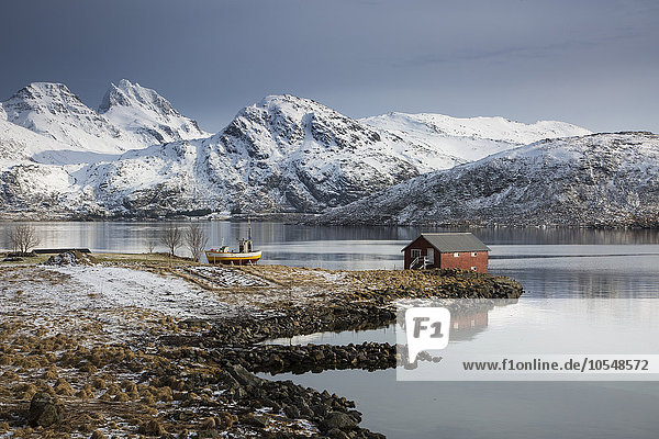 Fischerhütte in der kalten Bucht unter schneebedeckten Bergen  Norwegen