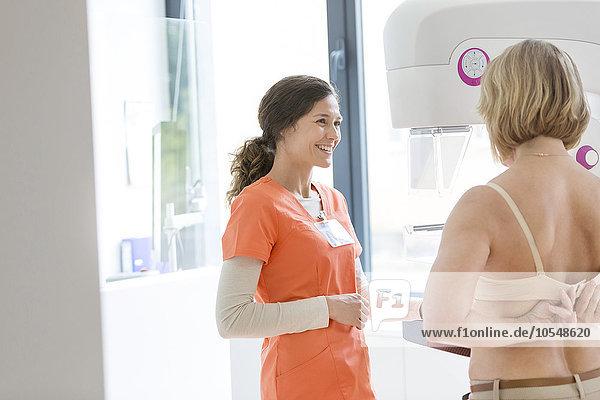 Krankenschwester hilft Patientin bei der Vorbereitung auf die Mammographie