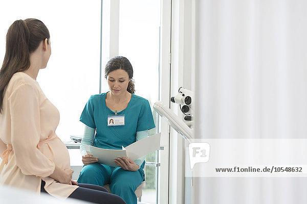 Krankenschwester und schwangere Patientin bei der Durchsicht der Krankenakte im Untersuchungsraum