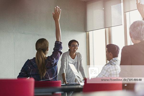 Lehrer und Schüler mit erhobenen Händen in der Erwachsenenbildung