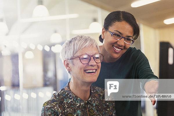 Lächelnde Geschäftsfrauen am Computer im Büro