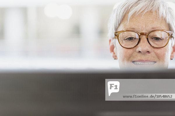 Senior Geschäftsfrau mit Brille am Computer