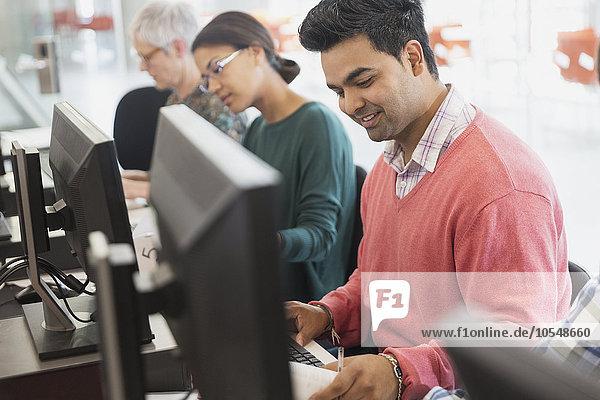 Lächelnder Student der Erwachsenenbildung am Computer im Klassenzimmer