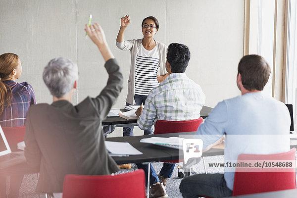 Lehrer ruft Schüler mit erhobener Hand im Klassenzimmer der Erwachsenenbildung an