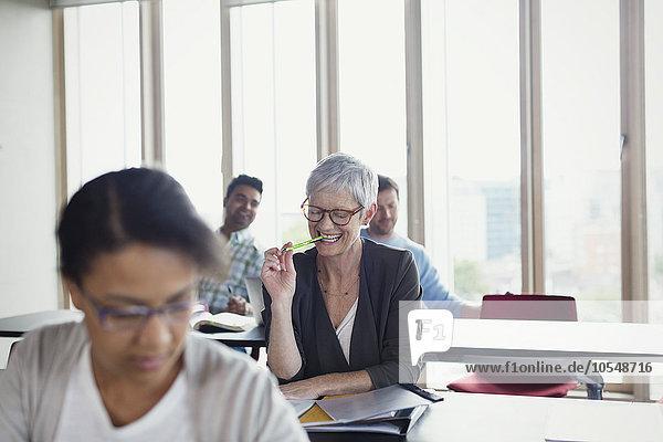 Lächelnde Seniorin im Klassenzimmer der Erwachsenenbildung