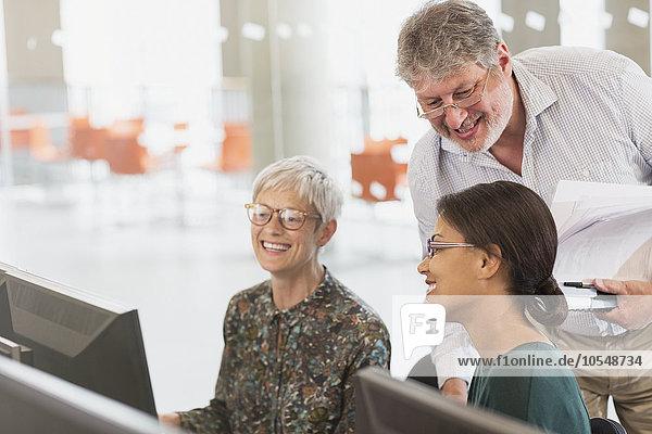 Lächelnde Schüler sprechen am Computer im Klassenzimmer der Erwachsenenbildung