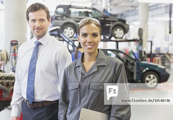 Portrait selbstbewusster Geschäftsmann und Mechanikerin in der Kfz-Werkstatt