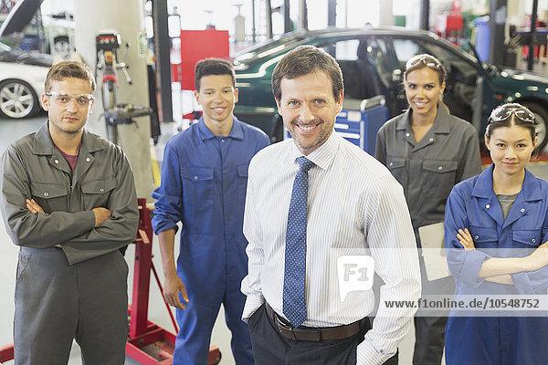 Portrait selbstbewusster Unternehmer und Mechaniker in der Kfz-Werkstatt