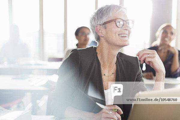 Lächelnde Seniorin am Laptop im Klassenzimmer der Erwachsenenbildung