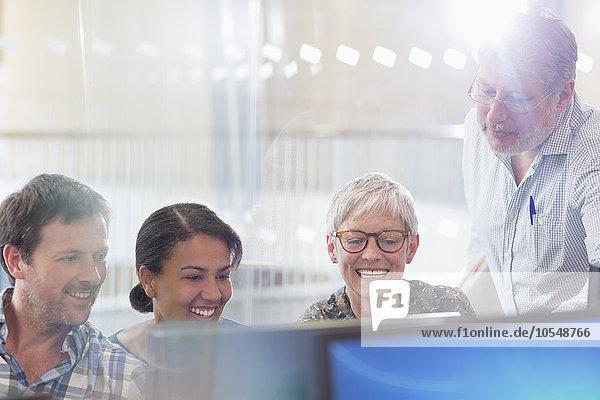 Studenten  die im Klassenzimmer der Erwachsenenbildung am Computer arbeiten