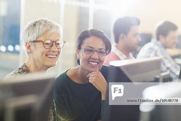 Lächelnde Frauen am Computer im Klassenzimmer der Erwachsenenbildung