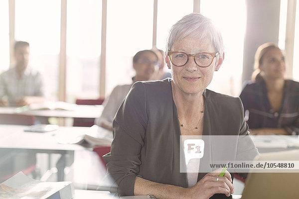 Portrait lächelnde Seniorin am Laptop im Klassenzimmer der Erwachsenenbildung