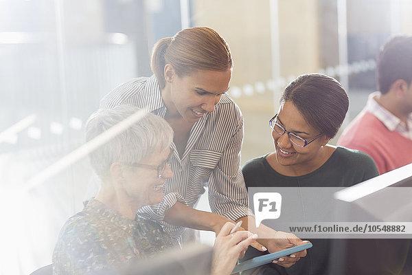 Geschäftsfrauen mit digitalem Tablett am Computer im Büro