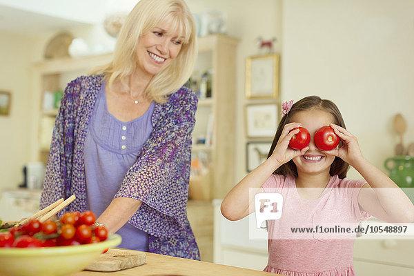 Portrait verspielte Enkelin, die in der Küche die Augen mit Tomaten bedeckt