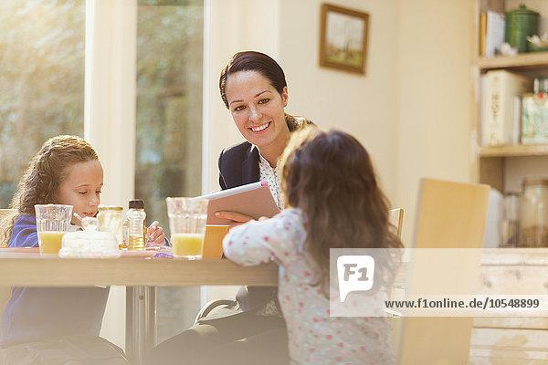 Arbeitende Mutter und Töchter am Frühstückstisch