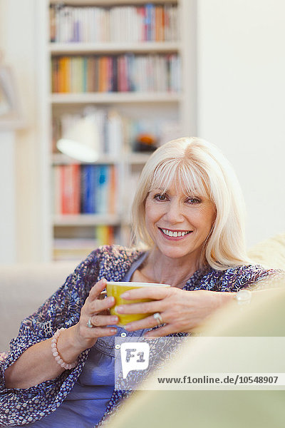 Portrait lächelnde Seniorin beim Kaffeetrinken auf dem Sofa