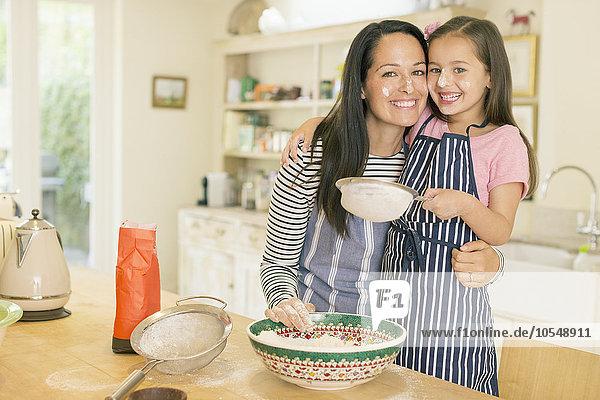 Portrait verspielte Mutter und Tochter beim Backen in der Küche mit Mehl auf den Gesichtern