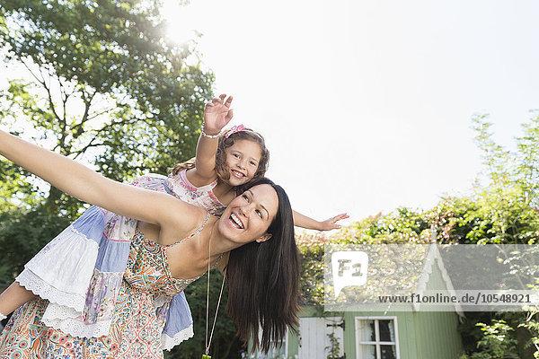 Sorglose Mutter Huckepack-Tochter mit ausgestreckten Armen im Hinterhof