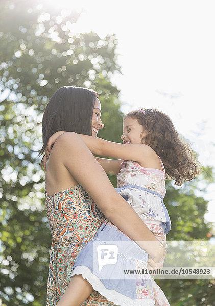 Zärtliche Mutter hält und umarmt Tochter im Freien