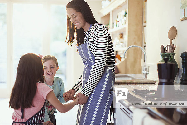 Mutter und Töchter halten Händchen in der Küche