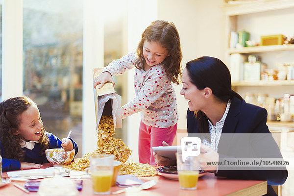 Mädchen, die viel Müsli am Frühstückstisch ausschenken
