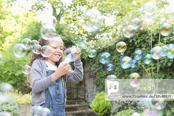 Mädchen bläst Blasen im Hinterhof